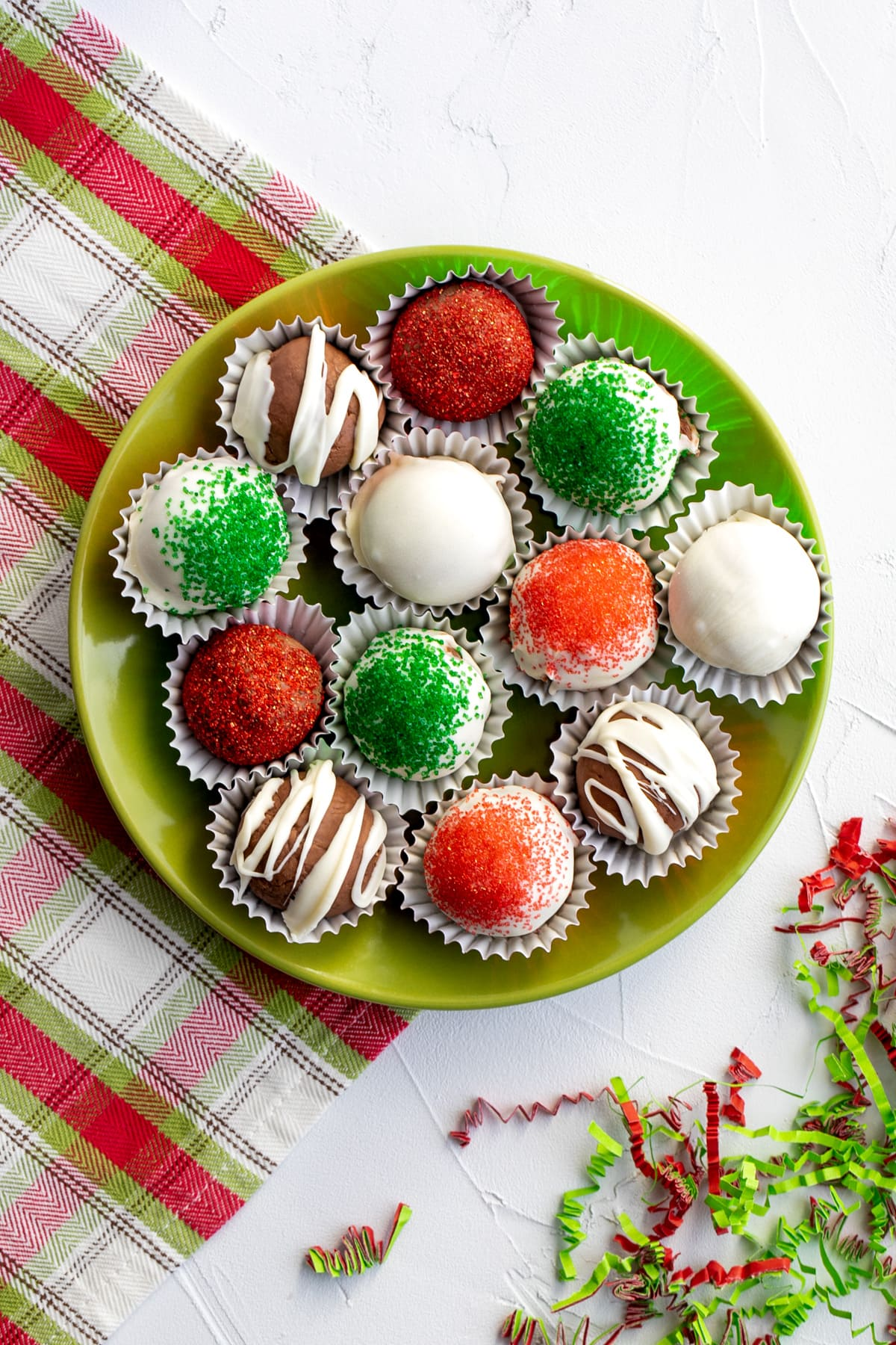 plate of Christmas chocolate truffles in green, red, and white on a green plate