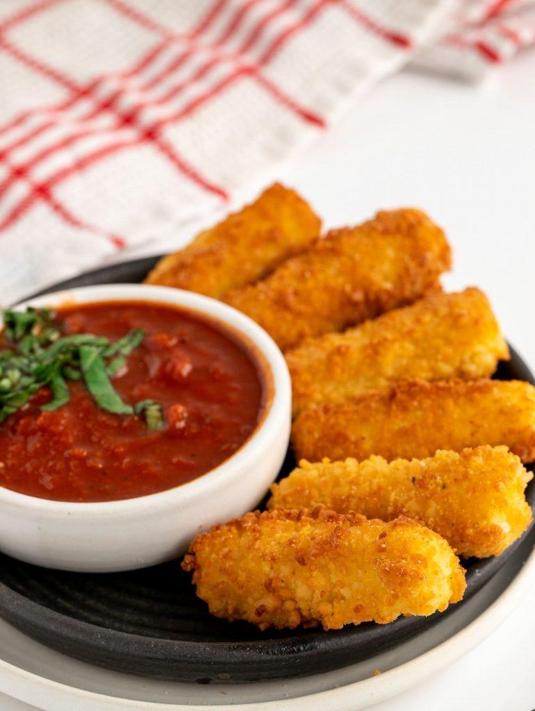 Pan fried mozzarella sticks on black plate with marinara sauce in a bowl
