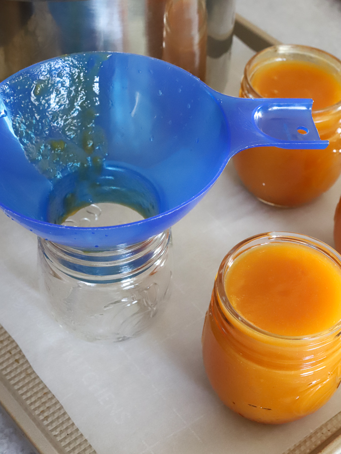 Fresh peach butter ladled into mason jar with canning tools and funnel
