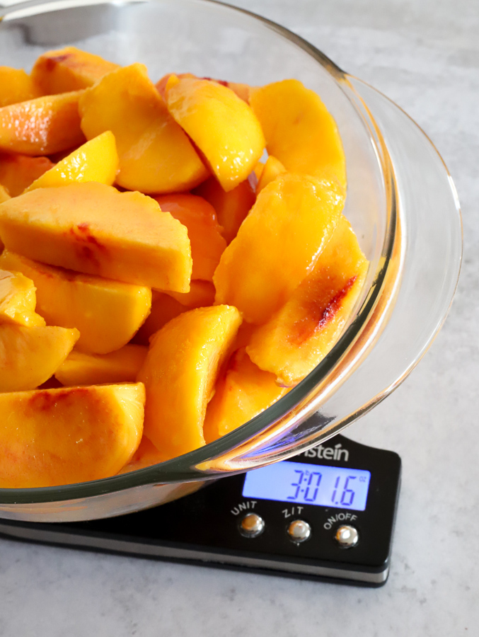 Three pounds of peeled and sliced peaches on a kitchen scale