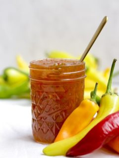 jar of pepper jelly with fresh peppers on white surface