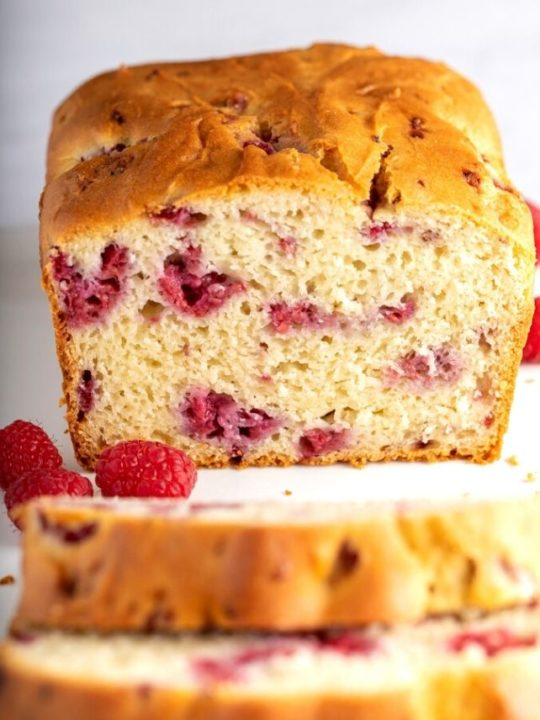 raspberry bread cut in half on white surface
