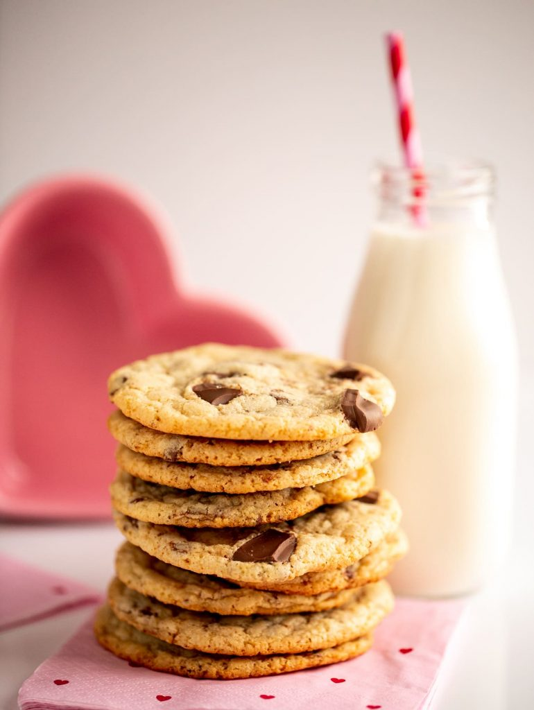 stack of chocolate chip cookies next to glass of milk