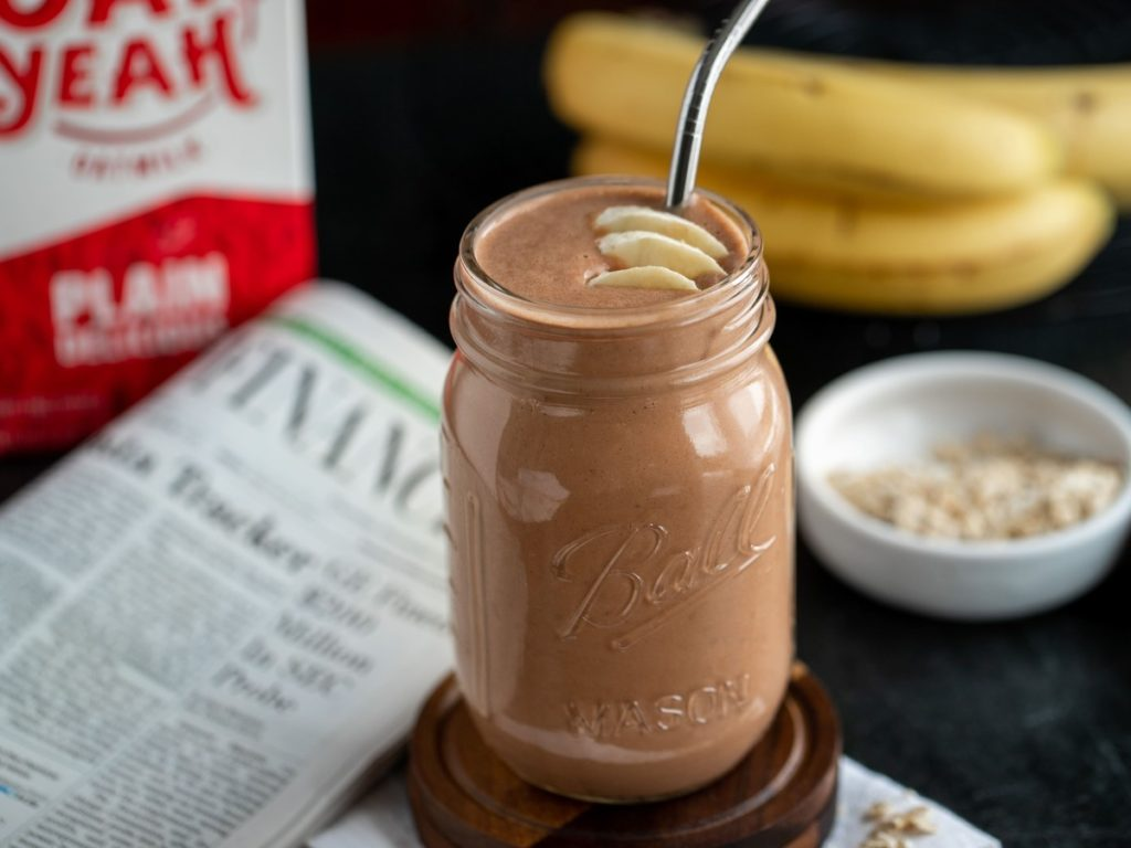 chocolate smoothie next to newspaper and Oat Yeah drink