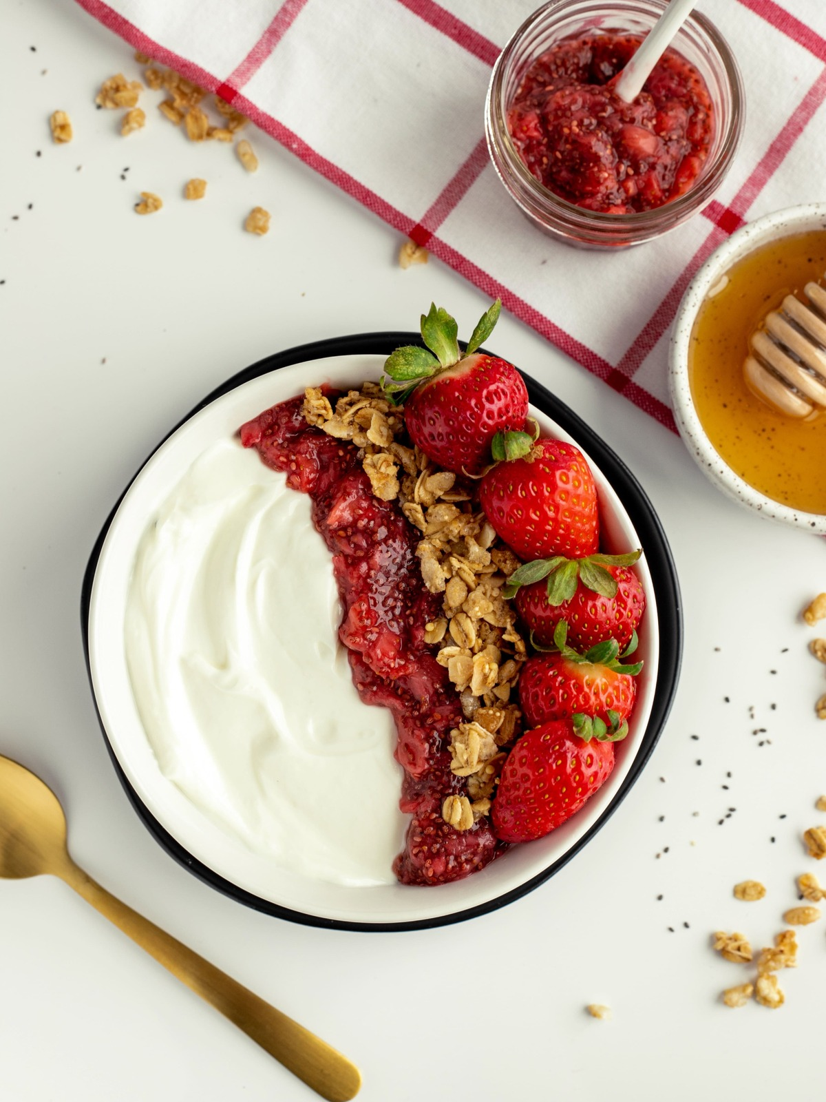 overhead view of ultra creamy yogurt with jam, granola and strawberries in black bowl