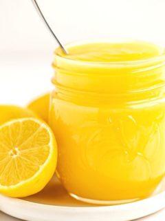 sliced fresh lemon next to mason jar filled with yellow lemon curd