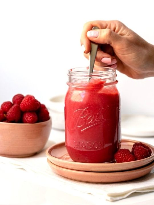 hand holding spoon that is dipped into a jar full of bright pink raspberry curd