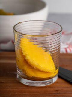 mango halves in a glass on a cutting board