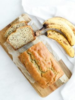 two slices of gf banana bread and loaf on wood cutting board