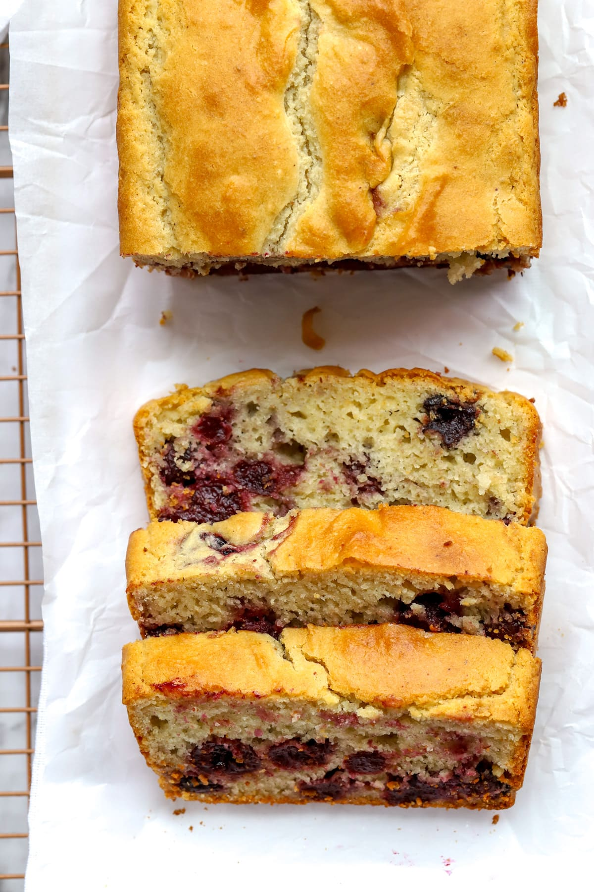 Overhead view of baked cherry bread on parchment paper with slices of bread with cherries