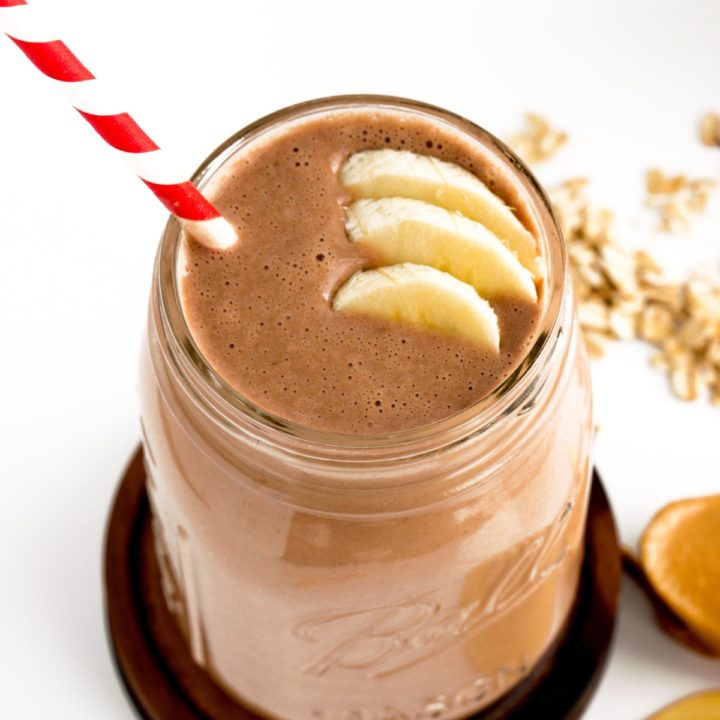 chocolate peanut butter smoothie with bananas and red and white straw