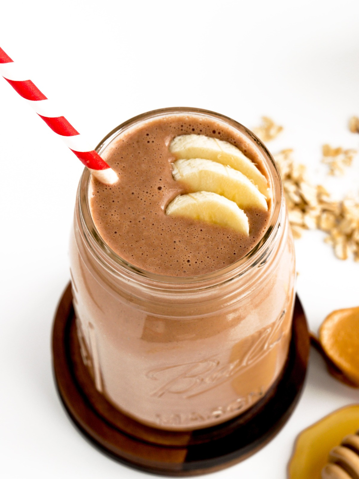chocolate peanut butter oat smoothie with bananas and red and white straw