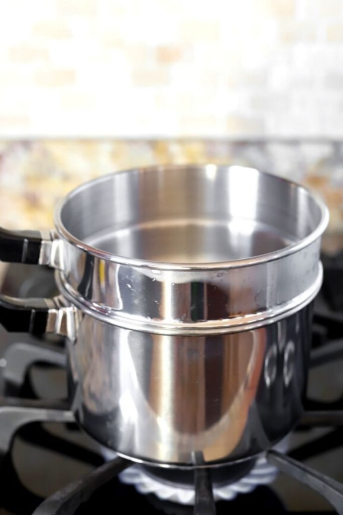 A double boiler sits on the stovetop with the gas lit