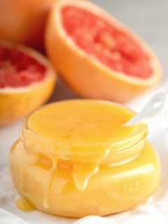 overflowing jar of grapefruit curd with fresh grapefruits in background