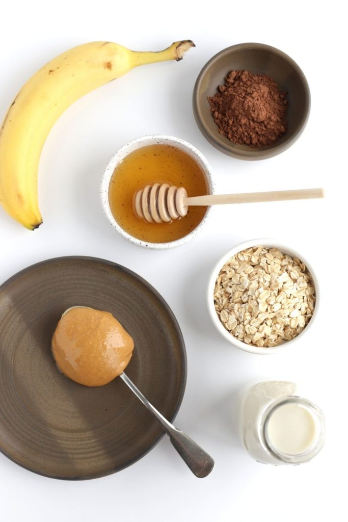 Ingredients for a chocolate peanut butter smoothie on white surface