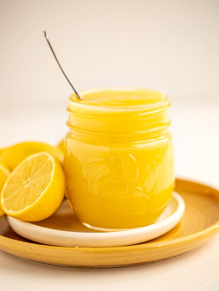bright yellow jar of lemon curd on white and yellow plates with fresh lemons
