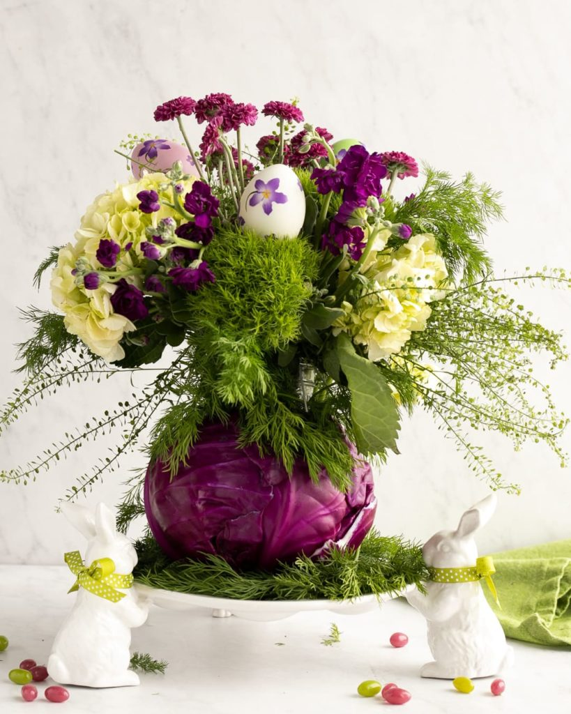 Easter centerpiece with purple, pink and white flowers in a cabbage base