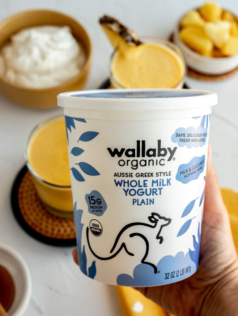 carton of Wallaby Organic Greek Yogurt with smoothie ingredients in background on table surface