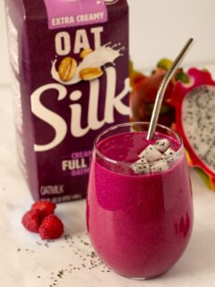 Dragon fruit smoothie in a glass with silver straw and Silk Oatmilk
