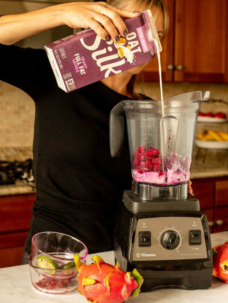 person pouring Silk Oatmilk into blender with dragon fruit and other ingredients