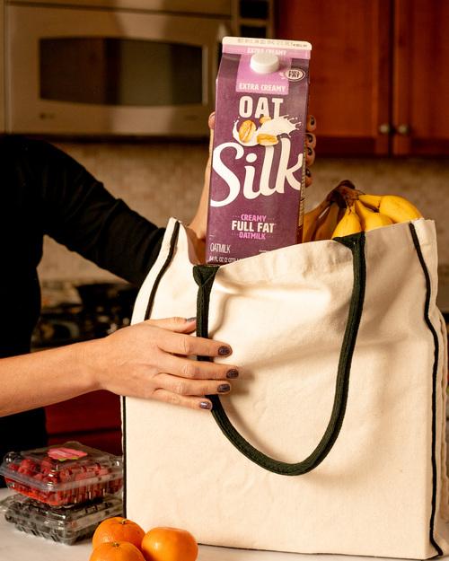 Silk Extra Creamy Oatmilk carton in a grocery bag