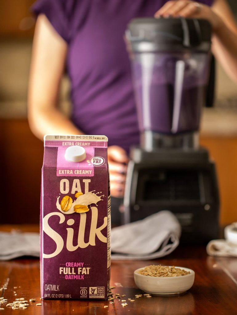 carton of Silk Oatmilk with person wearing purple shirt using blender to make blueberry smoothie