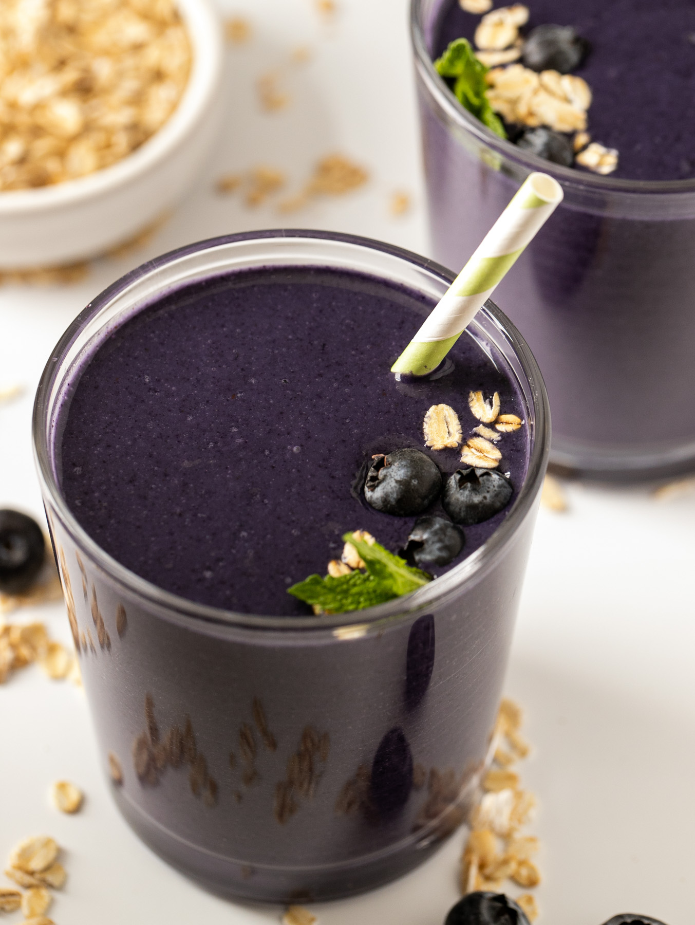 glass of dark blue blueberry oatmeal smoothie with oats and berries
