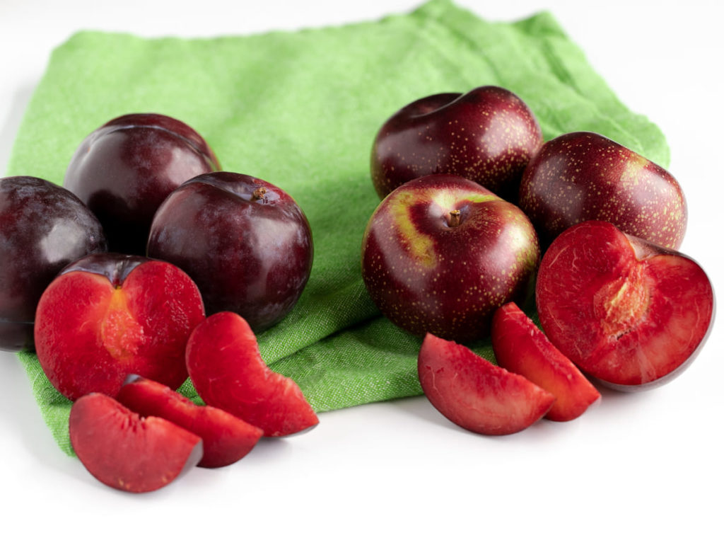 side by side comparison of fresh plums and Plumsicles on green napkin