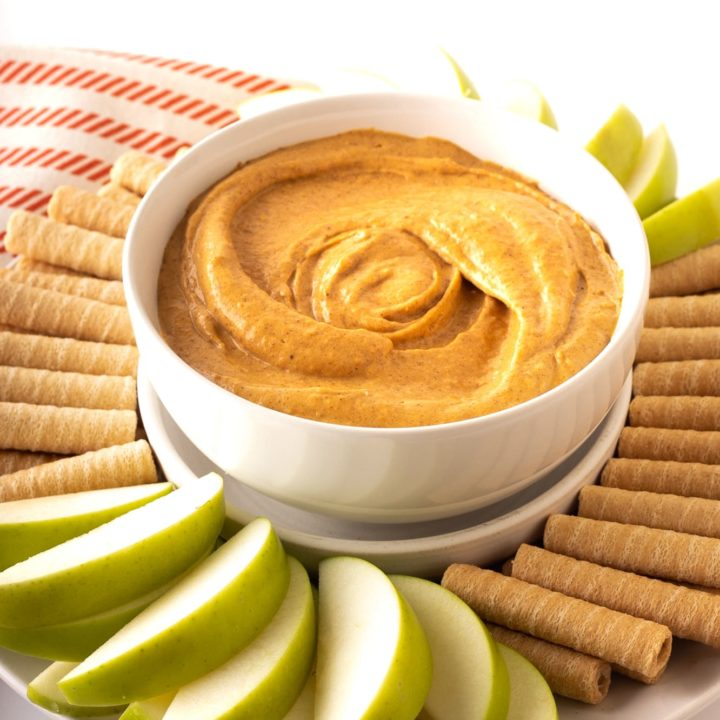 cream cheese pumpkin dip in white bowl with dippers